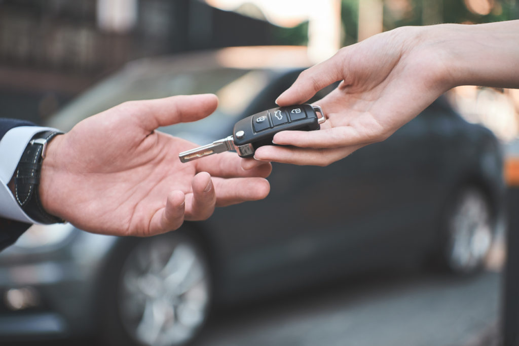 Young man receiving car key from saleswoman.
