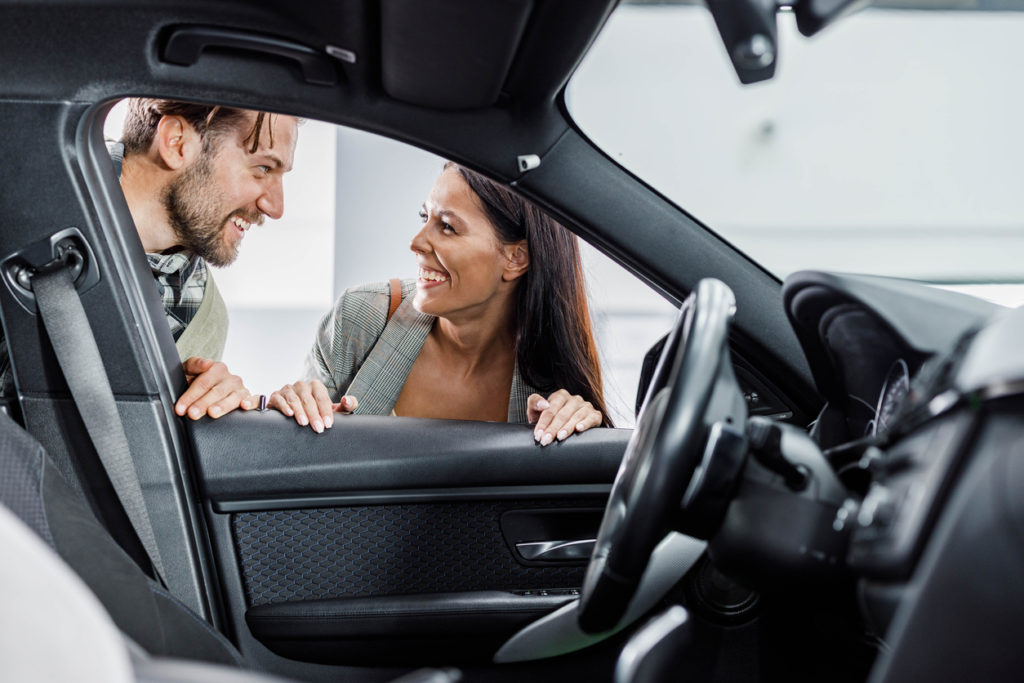Happy couple communicating while searching for the best car in a showroom.