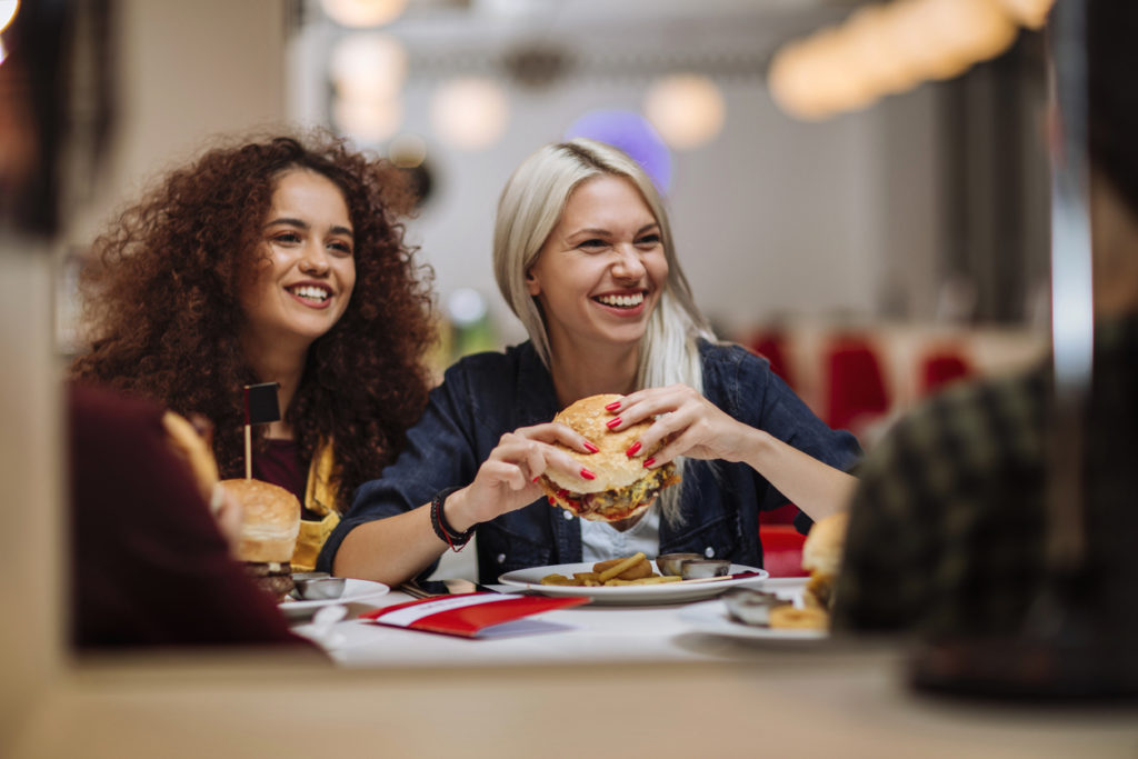 Two happy female friends eating burgers in a restaurant